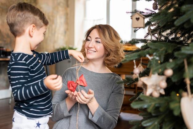 Menino e mãe segurando a decoração da árvore