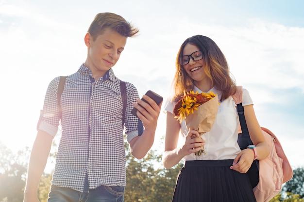 Menino e menina adolescentes caminhando ao ar livre