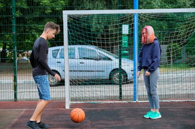 Menino e menina adolescentes jogando basquete de rua juntos, jovens com penteados da moda, jogando ao ar livre. estilo de vida saudável ativo, hobbies e lazer, conceito de adolescentes