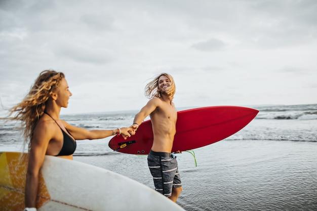 Menino e menina alegres correm para o mar e seguram pranchas para surfar