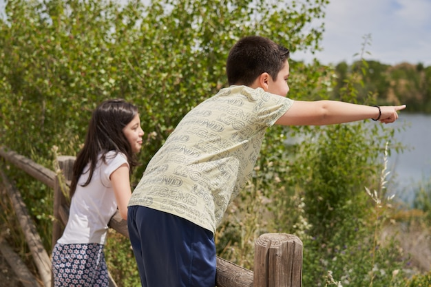 Menino e menina apontando parecendo feliz encostado em uma cerca de madeira no parque