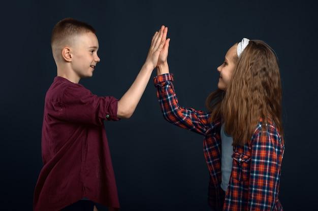 Menino e menina batem nas palmas das mãos. infância feliz, crianças se divertindo, crianças engraçadas isoladas em um fundo escuro, emoção infantil