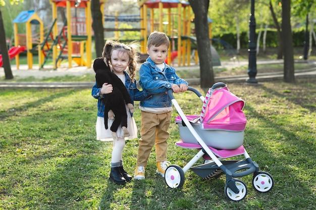 Menino e menina bebê andam com um carrinho de bonecas.