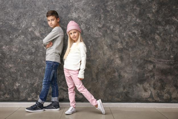 Menino e menina bonitos com roupas da moda perto da parede cinza