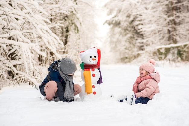 Menino e menina bonitos construindo um boneco de neve na floresta branca de inverno