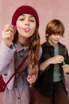 Menino e menina brincando com bolhas de sabão