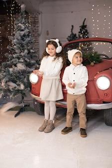 Menino e menina brincando com neve perto de um carro vermelho e uma árvore e luzes de natal