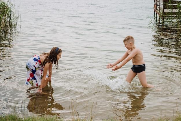 Menino e menina brincando na água às margens de um lago. férias de verão.