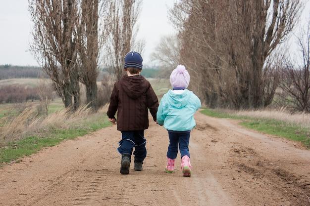 Menino e menina caminham pela estrada de mãos dadas.