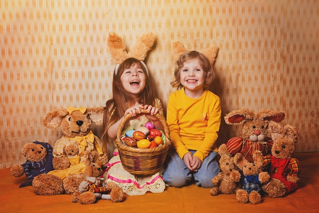 Menino e menina com as orelhas de coelho que sentam-se em torno de muitas lebres da palha e do luxuoso, estilo do vintage.