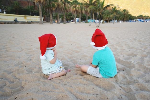 Menino e menina com chapéu de papai noel vermelho se divertindo na praia de areia do oceano crianças brincando no fundo da costa do mar