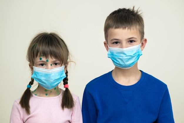 Menino e menina com máscara médica protetora azul doente com vírus da varicela, sarampo ou rubéola com erupções no corpo. proteção infantil durante epidemia de coronovírus. conceito de contágio covid-19.
