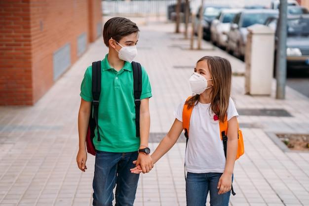 Menino e menina com mochilas e máscaras vão à escola na pandemia de coronavírus