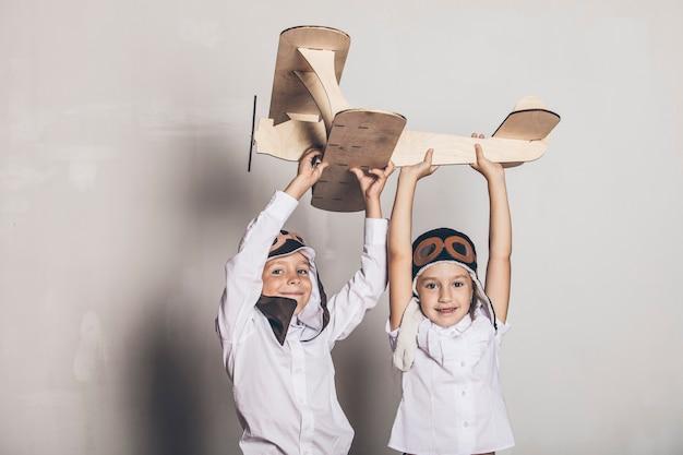 Menino e menina com modelo de avião de madeira e um boné com tampa