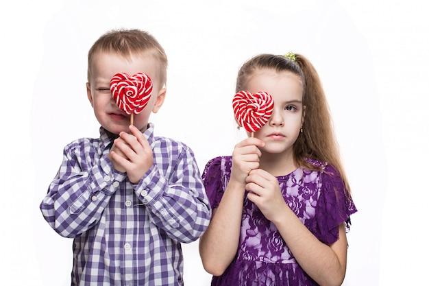Menino e menina com pirulitos. isolado no fundo branco