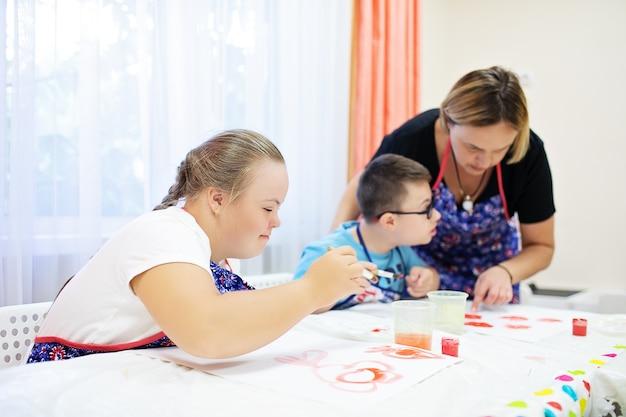 Menino e menina com síndrome de down desenhar em uma mesa sobre um fundo branco. foto de alta qualidade