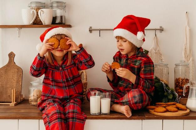 Menino e menina comendo biscoitos de natal e bebendo leite