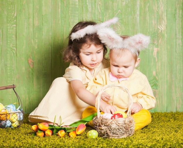 Menino e menina como coelhos da páscoa na grama com ovos coloridos