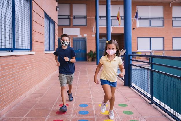 Menino e menina correndo no pátio da escola com máscara facial durante a pandemia de covid