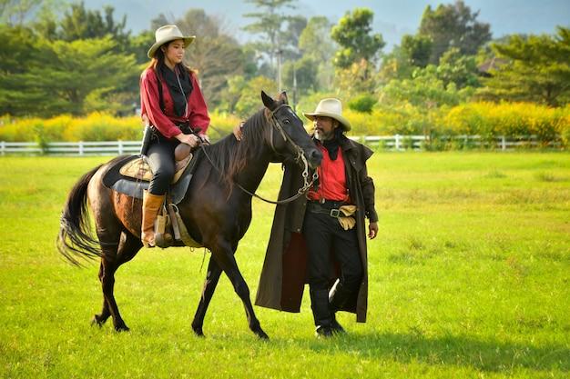 Menino e menina cowboy cavalgando no prado sol ameno pela manhã