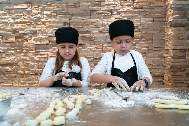 Menino e menina cozinhando uma massa vestidos como chefs profissionais