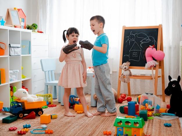 Menino e menina crianças gritando com dinossauros de brinquedo e brincando no quarto das crianças.