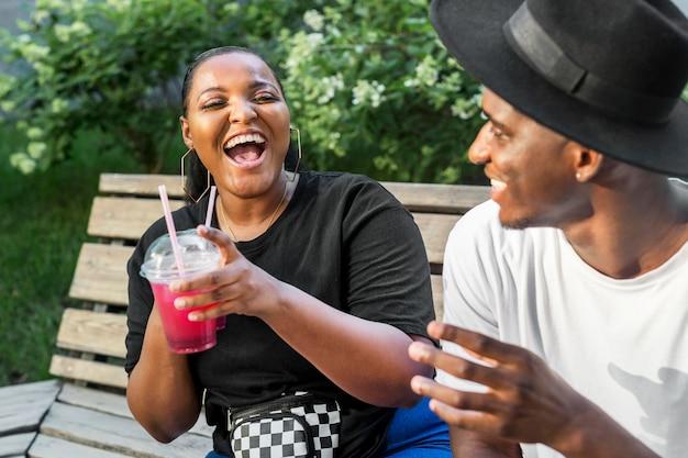 Menino e menina curtindo smoothies ao ar livre