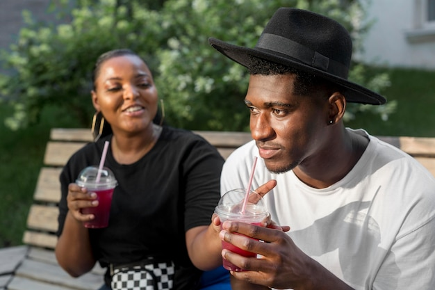 Menino e menina curtindo smoothies lá fora