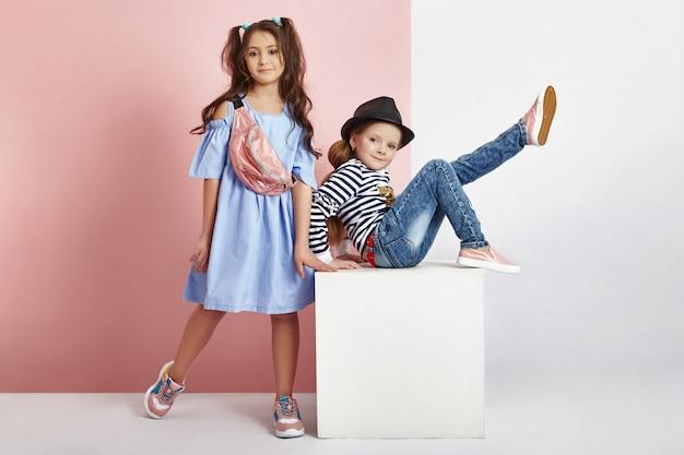 Menino e menina da moda em roupas elegantes no fundo da parede colorida. roupas brilhantes de outono em crianças, uma criança posando em um fundo rosa roxo colorido. rússia, sverdlovsk, 6 de abril de 2019