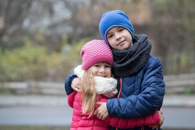 Menino e menina de duas crianças se abraçando ao ar livre, vestindo roupas quentes no frio do outono ou inverno.