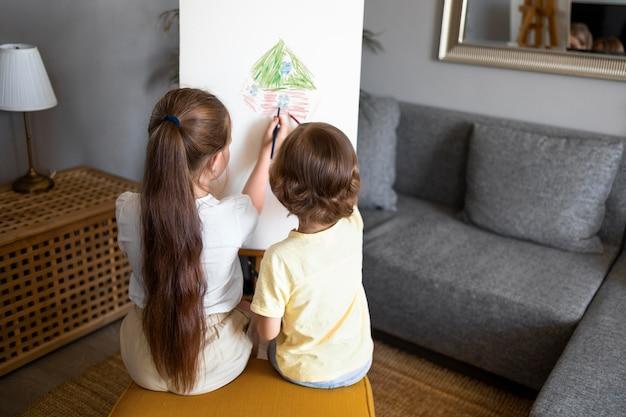 Menino e menina desenhando juntos em casa usando cavalete