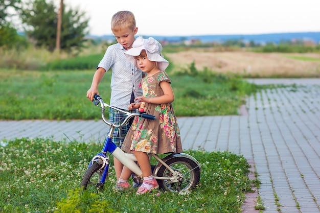 Menino e menina em bicicleta brincando ao ar livre em um dia ensolarado de verão