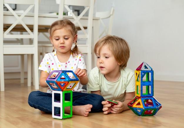 Menino e menina em casa brincando com brinquedos