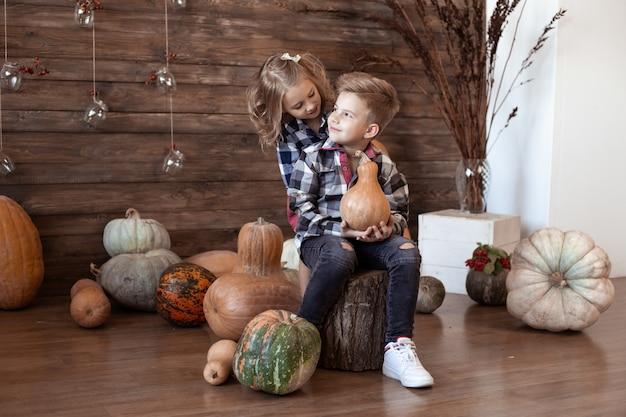 Menino e menina em casa no outono com abóboras