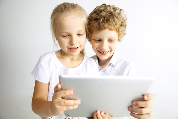 Menino e menina em jeans, melhores amigos ou irmão e irmã se divertindo. fazendo uma selfie no tablet. conceito de infância, educação, férias ou lição de casa, tecnologias modernas.