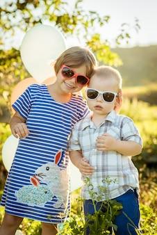Menino e menina em óculos de sol abraçando a natureza
