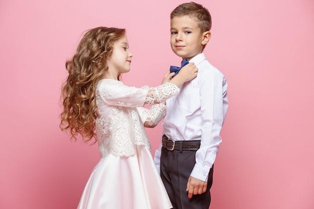 Menino e menina em pé no rosa