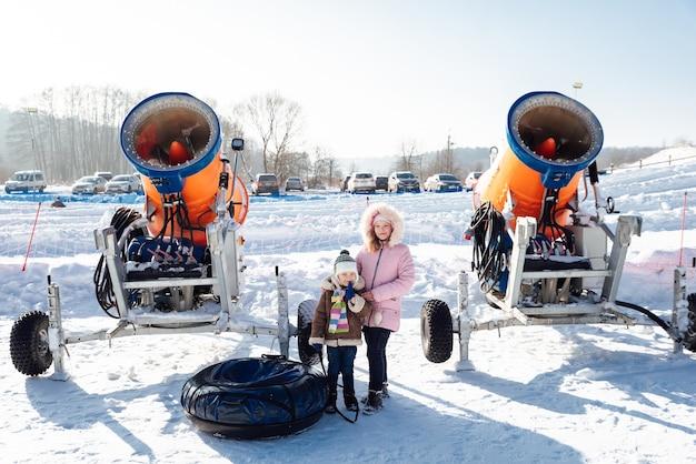 Menino e menina em pé perto de um canhão de neve