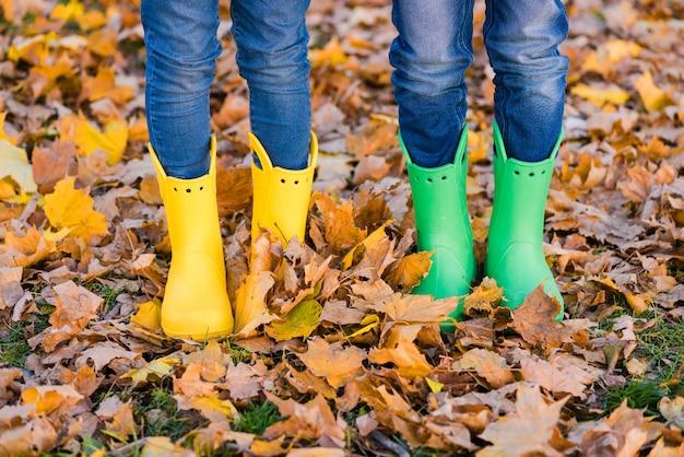 Menino e menina em sapatos amarelos e verdes no outono