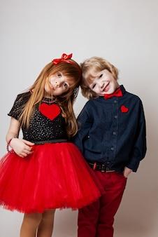 Menino e menina em um fundo branco, coração vermelho
