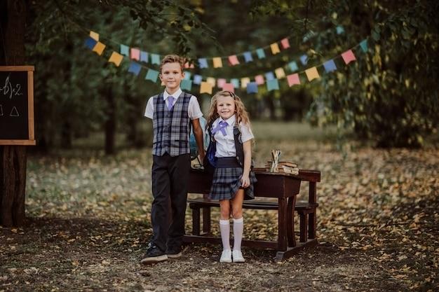 Menino e menina em uniforme escolar posando perto de uma velha mesa de madeira no parque