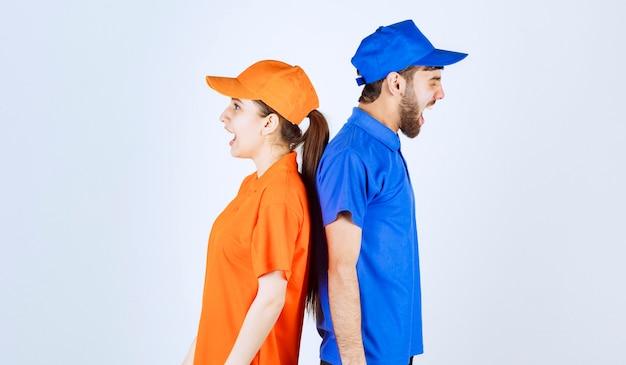Menino e menina em uniformes azuis e amarelos, encostados um no outro e gritando.