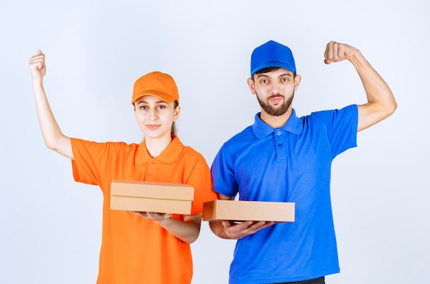 Menino e menina em uniformes azuis e amarelos segurando vários pacotes para levar e seu poder.