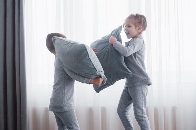 Menino e menina encenaram uma luta de travesseiros na cama do quarto. crianças travessas batem nos travesseiros. eles gostam desse tipo de jogo.