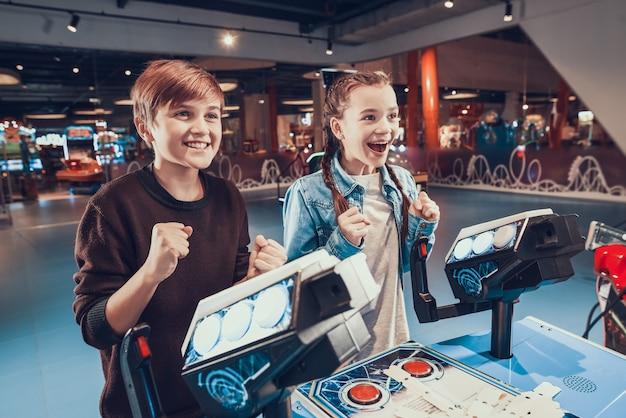 Menino e menina estão pilotando naves espaciais azuis jogando no fliperama