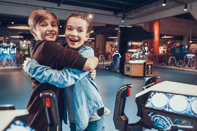 Menino e menina estão pilotando naves espaciais jogando no arcade.