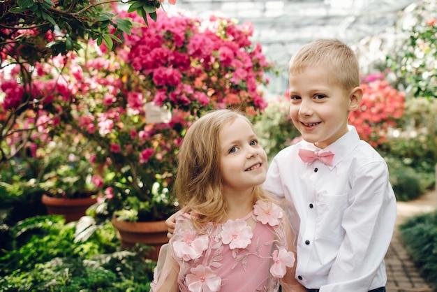 Menino e menina felizes caminhando abraçados no jardim florido de primavera
