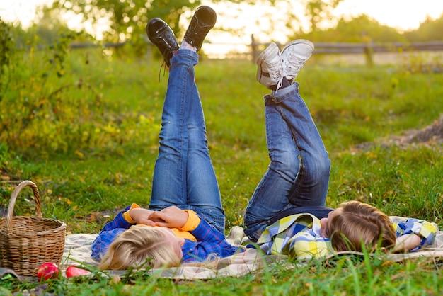 Menino e menina felizes e sorridentes, deitados juntos na grama