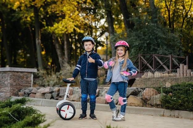 Menino e menina felizes em pé e passear no parque em segways e scooters durante o pôr do sol