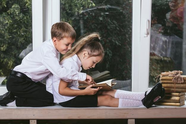 Menino e menina felizes sentados no parapeito da janela lendo livros ao fundo